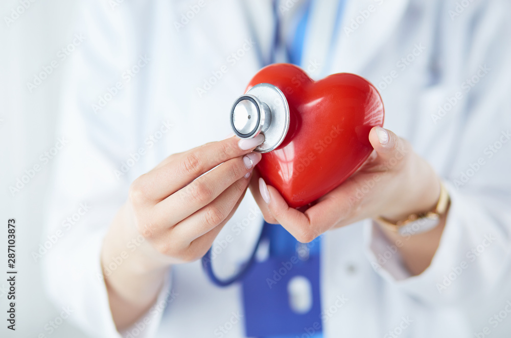 Fototapeta A doctor with stethoscope examining red heart, isolated on white background