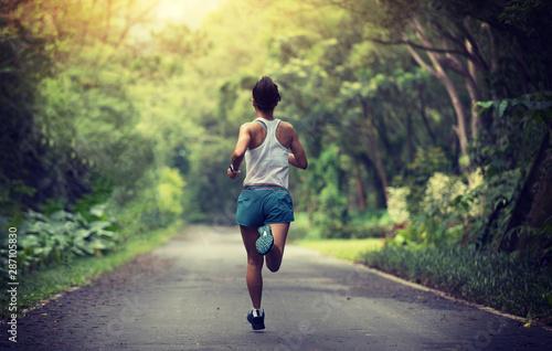 Fototapeta Female runner running at summer park trail