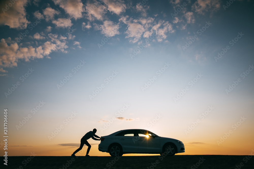 Fototapety, obrazy: Silhouette of man driver pushing his car along on an empty road after breakdown at sunset, copy space, side view. Road trip, trouble on the road