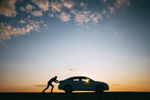 Silhouette Of Man Driver Pushing His Car Along On An Empty Road After Breakdown At Sunset, Copy Space, Side View. Road Trip, Trouble On The Road