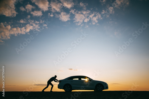 Silhouette of man driver pushing his car along on an empty road after breakdown at sunset, copy space, side view Canvas Print