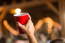 Woman's Hand Holding Up Red Solo Cup In Cheer