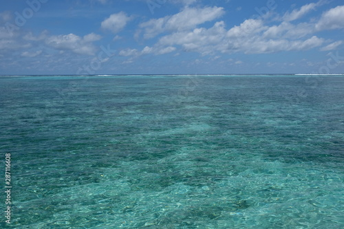 Photo wide green sea horizon under white cloud sunny blue sky in Maldives