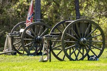American Civil War Era Cannons And A Confederate Flag On A Battlefield During A Civil War Re-enactment