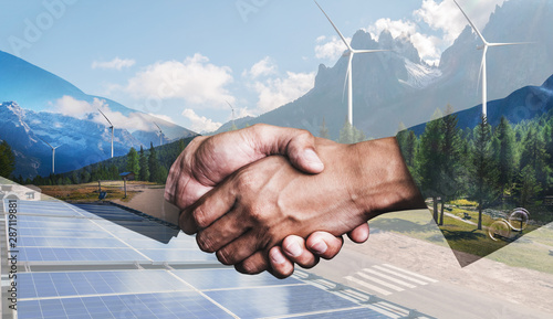 Obraz Double exposure graphic of business people handshake over wind turbine farm and green renewable energy worker interface. Concept of sustainability development by alternative energy. - fototapety do salonu