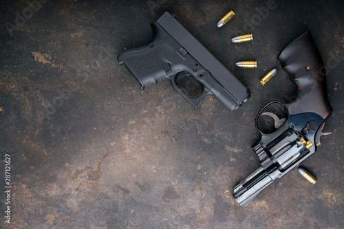 Gun with ammunition on iron dark background. Canvas Print