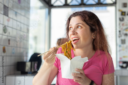 Valokuvatapetti Close-up portrait of young pretty girl eating chinese noodles with wooden chopsticks sitting in a cafe