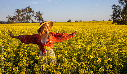 Keuken foto achterwand Honing Laughing young lady with straw hat in yellow Canola Field in Western Australia