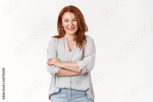 Stampa su Tela  Caring lovely happy middle-aged redhead woman cross arms chest smiling joyfully
