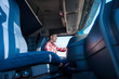 Professional truck driver steering and driving vehicle on highway. Inside view of trucker driving long vehicle. Transportation and distribution services.