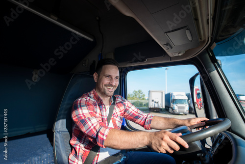 Fotomural  Shot of professional truck driver in casual clothing wearing seat belt on and driving his truck to destination
