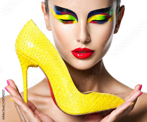 Fotografia, Obraz beautiful woman with vivid make-up of eyes holds the yellow high heel