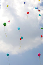 Colored Balloons Fly Into The Sky With Clouds During The Celebra