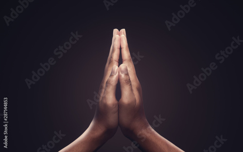 Leinwanddruck Bild - Lunatictm : Praying hands with faith in religion and belief in God on dark background. Power of hope or love and devotion. Namaste or Namaskar hands gesture.