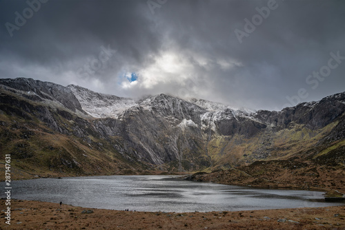 Stampa su Tela Beautiful moody Winter landscape image of Llyn Idwal and snowcapped Glyders Moun