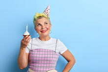 Romantic Glamour Woman With A Birthday Cake Posing To The Camera, Looking Aside. Close Up Portrait. Isolated Blue Background, Studio Shot.