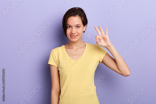 Photo attractive happy woman showing ok sign at the camera over blue background, closeup portrait, body language, everything is ok,allright