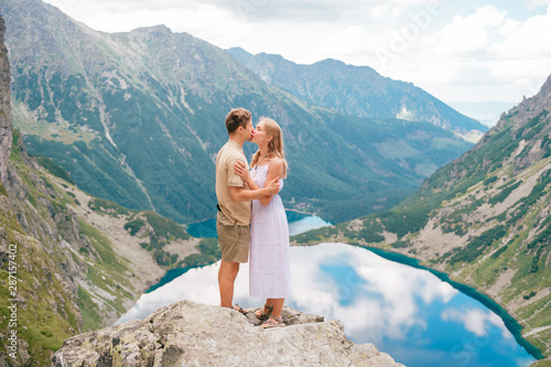 Happy loving couple standing together at stone in High Tatra national park in Poland with a picturesque landscape on background Wallpaper Mural