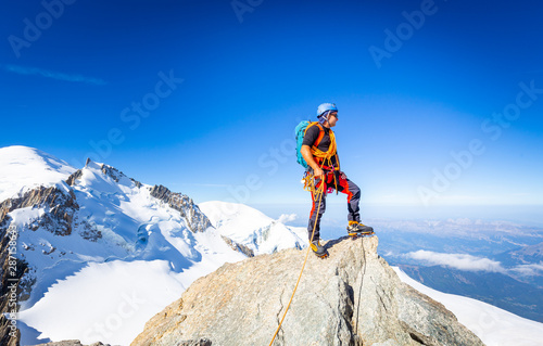 Alpinist mountaineer standing rock cliff mountain summit. Canvas Print