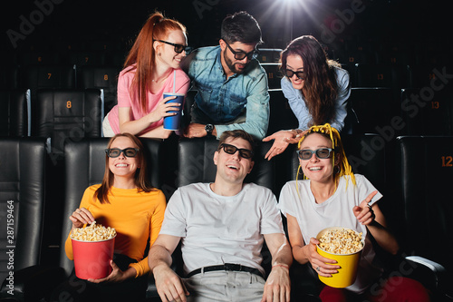 Fotografija Multiethnic cheerful audience sitting at the cinema and watching movie, students