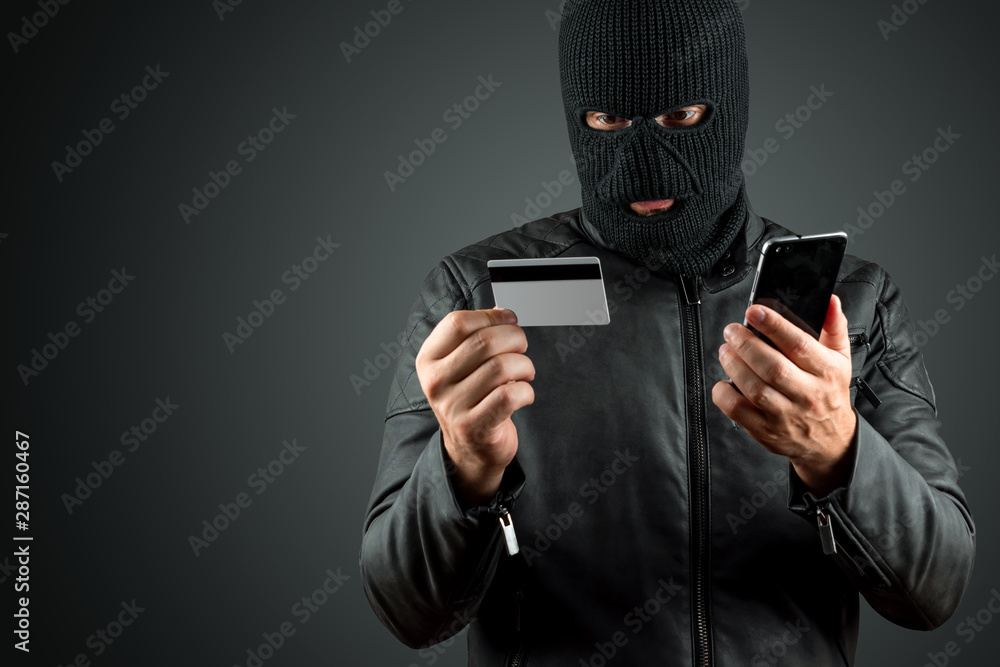 Fototapeta Robber, a thug in a balaclava holds a credit card in his hands on a dark background. Robbery, hacker, crime, theft. Copy space.