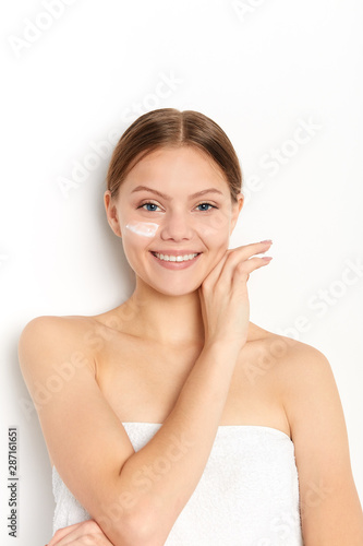 Close up portrait of a laughing positive beautiful half naked girl applying face cream isolated over white background, beauty, treatment - 287161651