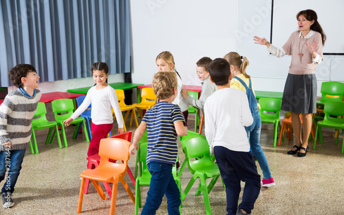 Kids and teacher playing musical chairs Fototapeta