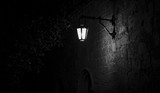Fototapeta Uliczki - Spooky black and white alley with a lit street lamp