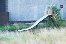 Play Park Derelict Abandoned Slide In Overgrown Grass At Playground