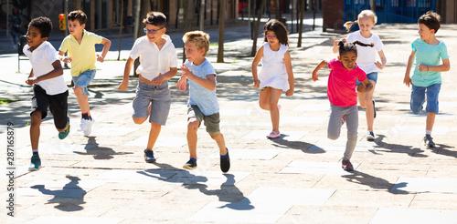 Fotomural  Group of joyful children running down the city street