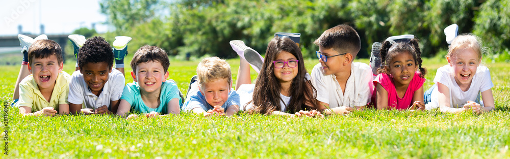 Fototapety, obrazy: Team of friends children resting on grass together in park