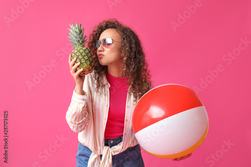 Valokuvatapetti Happy African-American woman with ball and pineapple on color background