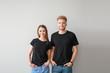 Leinwandbild Motiv Couple in stylish t-shirts on light background