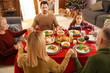 Family praying before having Christmas dinner at home