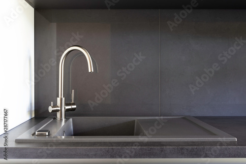 Fotomural  Grey granite kitchen sink with a stainless steel tap for filtered water on a grey benchtop and grey backsplash