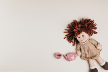 A Doll And Toy Tea Set On A White Background