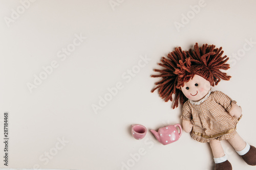 Fototapeta A doll and toy tea set on a white background