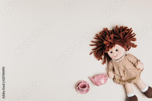 Fototapeta A doll and toy tea set on a white background