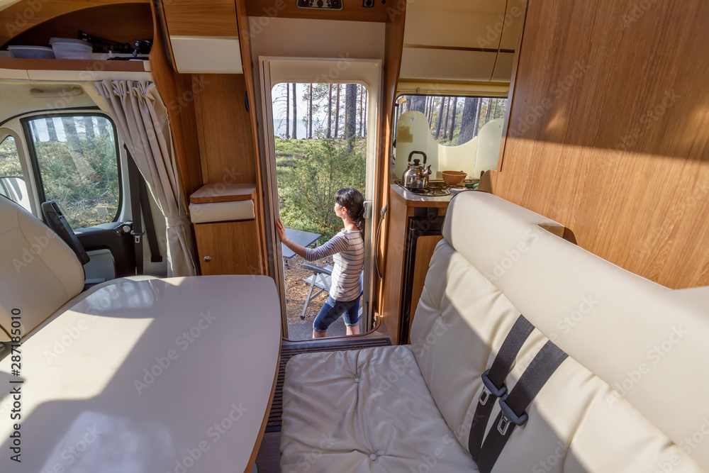 Fototapeta Woman in the interior of a camper RV motorhome with a cup of coffee looking at nature.