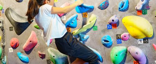 Obraz na plátně  [ボルダリング] ボルダリングスタジオで壁に登る前に滑止めをつけて気合いを入れる女子小学生クライマー
