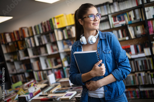 Fotobehang Hoogte schaal College woman studying at the library looking happy