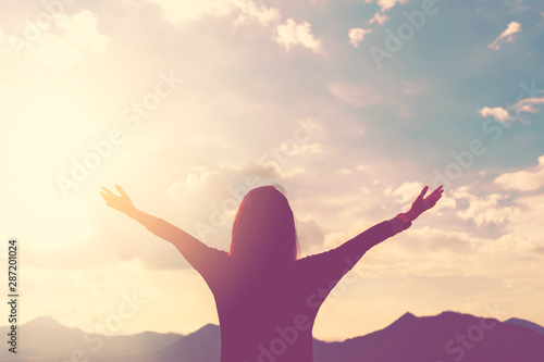 Obraz na plátně  Copy space of woman rise hand up on top of mountain and sunset sky abstract background
