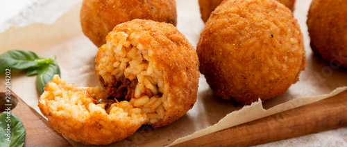 Homemade fried Arancini with basil on a rustic wooden board, side view Wallpaper Mural