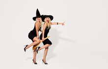 Two Beautiful Young Tweens Women Tweens In Black Halloween Witch Costumes With Hat And Broom Having Fun Over White Background. Copy Space For Text, Point To The Right