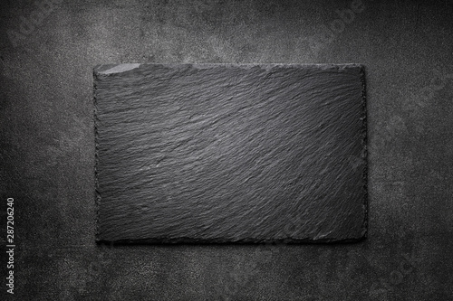 Fototapeta Black slate board on dark stone texture top view