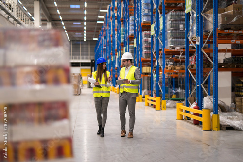 Carta da parati  Warehouse workers walking through large storage department discussing about distribution and logistics