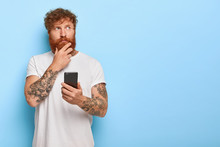 Horizontal Shot Of Serious Contemplative Adult Man Touches Thick Red Beard, Holds Mobile Phone, Browses Newsfeed Online, Thinks Over Recent News, Has Tattooed Arms, Wears Casual White T Shirt