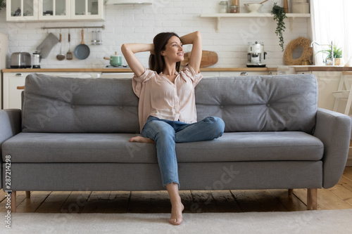 In cozy living room happy woman sitting on couch alone - 287214298