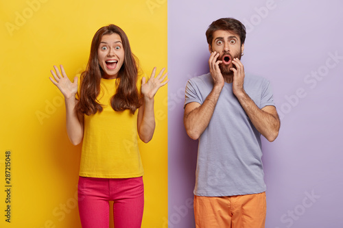 Photo of cheerful excited woman raises hands and exclaims something emotionally, shocked man stares with great wonder, dressed casually, stand against of two colored background Fototapet