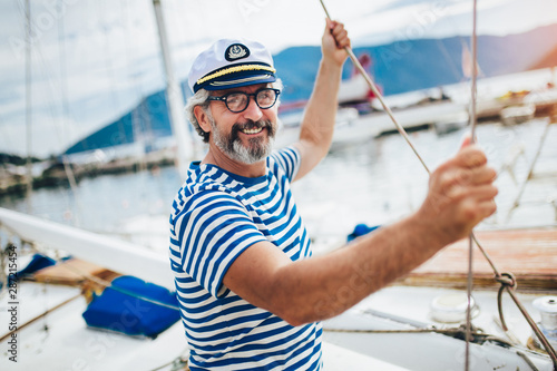 Foto Mature man standing and laughing at helm of sailboat out at sea on a sunny afternoon